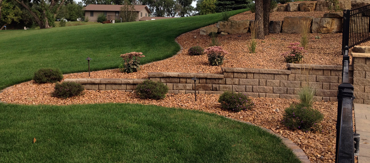 High Quality Backyard Landscaping With Plants And Retaining Wall